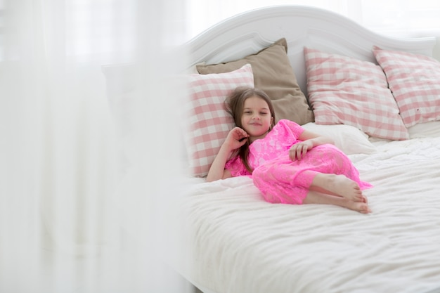 Pretty little girl in pink princess dress in white bed with cushin