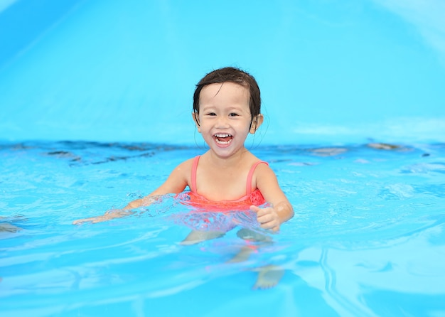 Довольно маленькая девочка играет в бассейне на открытом воздухе