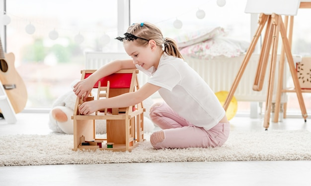 Pretty little girl plays with wooden dollhouse in children's room