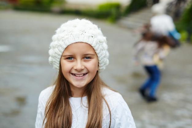 Bambina graziosa che posa alla macchina fotografica