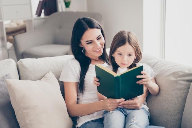 예쁜 소녀는 실내 집에서 그녀의 엄마와 함께 재미있는 책을 읽고