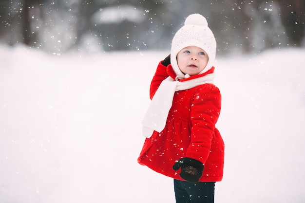 Pretty little girl in red coat in winter forest. little girl having fun on winter day. cheerful little baby girl in gloves and white hat runs on snow white