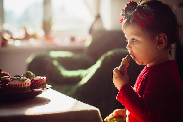 Pretty little girl in red dress eats cookie standing before the table