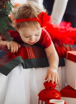 Pretty little girl in red dress looks funny