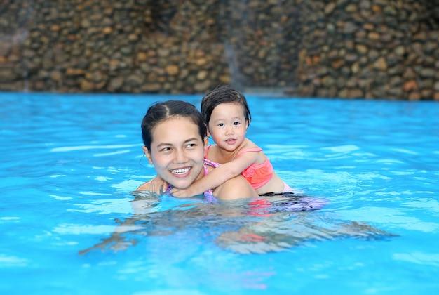 Хорошенькая девочка едет назад своей матерью в бассейне на открытом воздухе