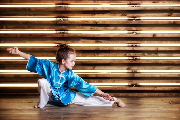 Pretty little girl in the room in sportswear for martial arts is wushu or kung fu