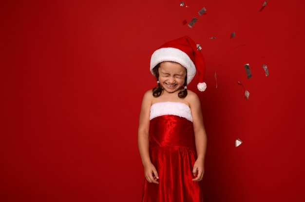 Pretty little girl in santa carnival attire rejoices, poses with closed eyes, cute smile against red background with falling sequins and confetti. christmas, new year celebration concept, copy space