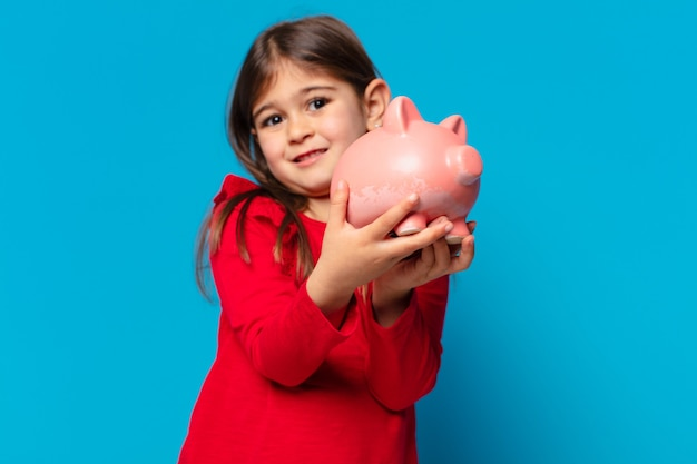 Pretty little girl scared expression and holding a piggy bank