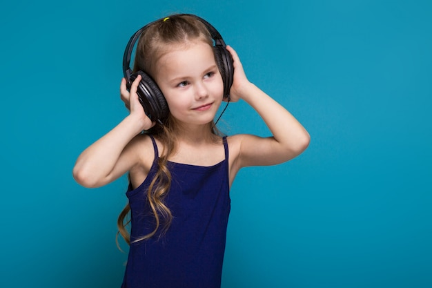 Pretty, little girl in shirt and earphones with brunet hair