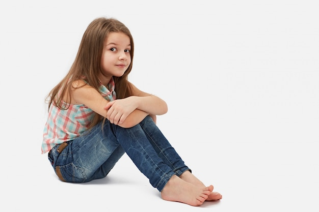 Pretty little girl sitting on the floor, isolated over white