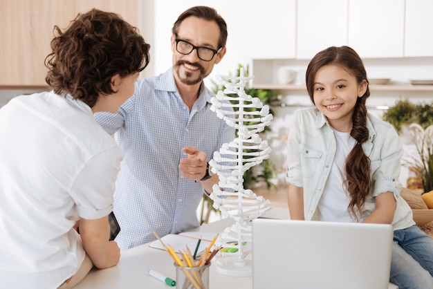 Pretty little girl sitting on the kitchen counter next to 3d dna model and posing while her father and brother talking about school