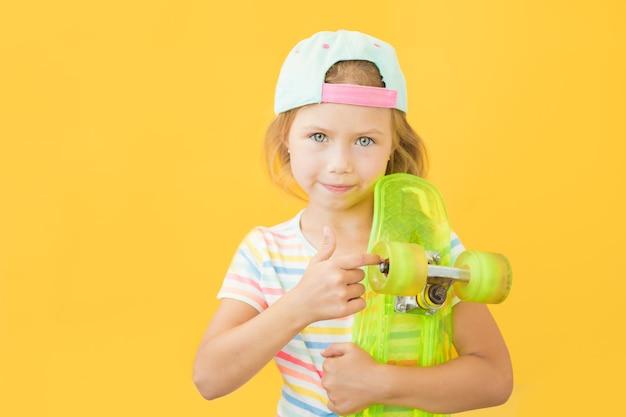 Милая маленькая девочка, стоящая на желтом фоне с зеленым коньком