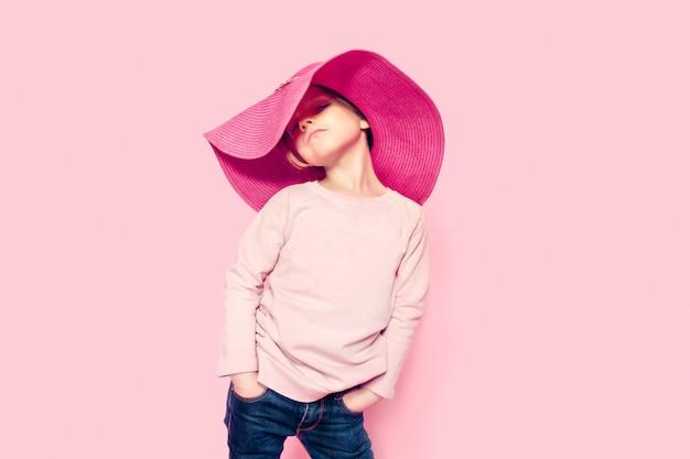 A pretty little girl in a studio wearing summer hat