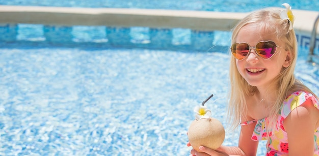 Pretty little girl in swimming pool, summer vacations.