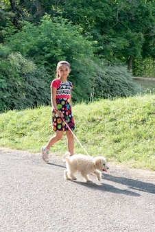 Pretty little girl taking her dog for a walk