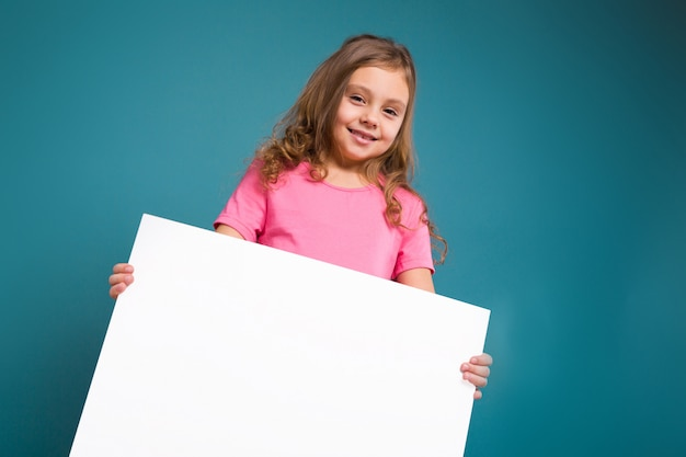Pretty, little girl in tee shirt with brown hair hold clean blank placard