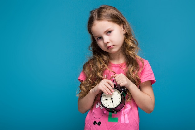 Pretty, little girl in tee shirt with brunet hair, with clock in hands