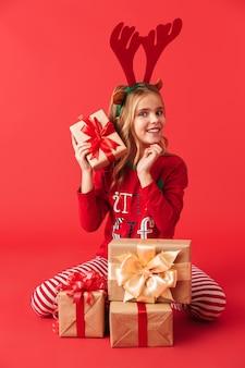 孤立して座って、プレゼントボックスのスタックを保持しているクリスマス鹿の角を身に着けているかわいい女の子