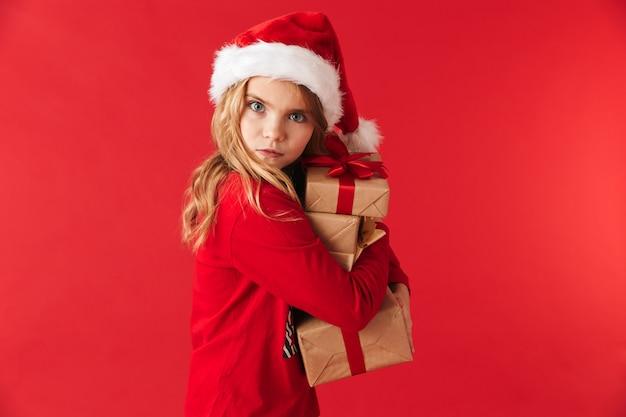 Симпатичная маленькая девочка в рождественской шляпе стоит изолированно, держа стопку настоящих коробок
