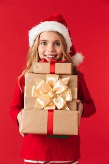 선물 상자의 스택을 들고 절연 서 크리스마스 모자를 쓰고 예쁜 소녀