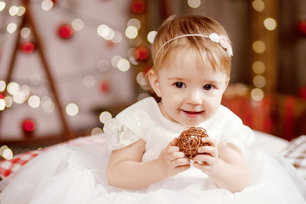 Pretty little girl in white dress playing and being happy about christmas tree and lights.