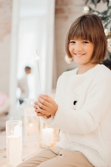Pretty little girl in white sweater before a christmas tree