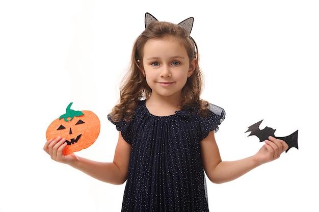 아름다운 이브닝 드레스를 입은 고양이 귀 모양의 고리를 가진 예쁜 소녀는 펠트 컷 호박과 수제 박쥐를 들고 카메라를 바라보며 미소를 짓고 있습니다. 흰색 배경 복사 공간에 고립
