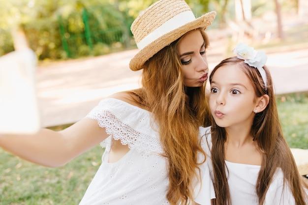 大きな茶色の目を持つかわいい女の子は、彼女の母親がスマートフォンを持っている間、驚いた表情でポーズをとっています。額で娘にキスして自分撮りをするスタイリッシュな女性。
