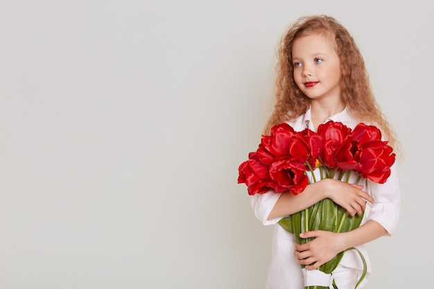 Pretty little girl with blonde wavy hair wearing white clothing holding red tulips in hands and looking aside