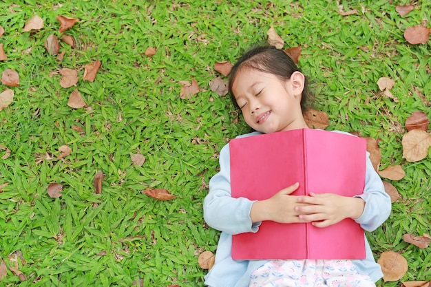 Pretty little girl with book lying on green grass with dried leaves in the summer garden.