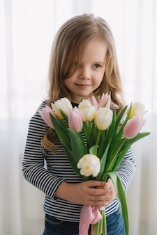 Pretty little girl with bunch of tulips on a happy mothers day. makes a gift for her mom.