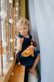 Симпатичная маленькая девочка со светлыми волосами в синем платье держит свою прекрасную игрушку, сидит в детской на подоконнике и улыбается
