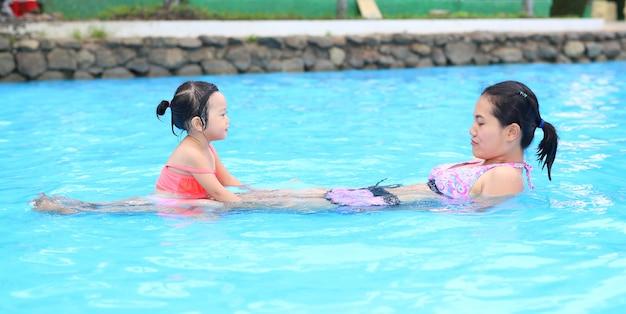 Довольно маленькая девочка с матерью в бассейне на открытом воздухе
