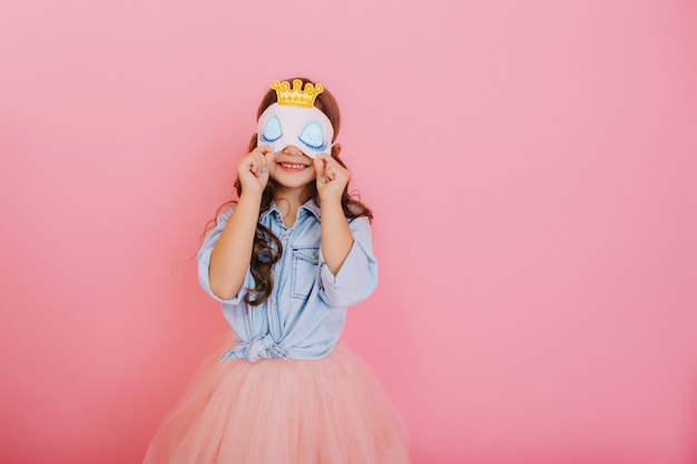 Pretty little girl with long brunette hair in tulle skirt holding sleep mask with blue eyes and golden crown isolated on pink background. celebrating birthday party, having fun at carnival for kids