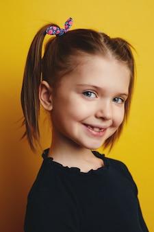Милая маленькая девочка с хвостиками очаровательно позирует на желтом фоне Premium Фотографии