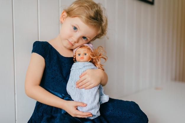 Симпатичная маленькая девочка с короткими светлыми волосами в синем платье держит свою прекрасную игрушку барби, сидит в яркой детской комнате и улыбается