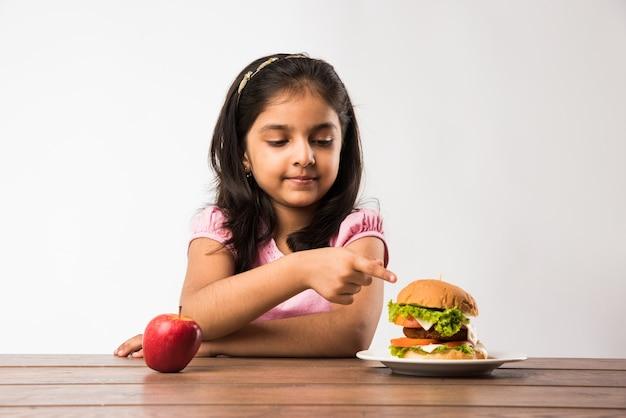 新鮮なリンゴとハンバーガーのどちらかを選択できないかわいいインド人またはアジア人の女の子、健康的な食事の概念