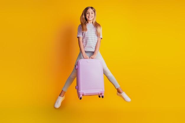 Довольно маленькая девочка ребенок прыгает на желтом фоне держит чемодан
