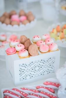 Довольно маленькие розовые и белые торты и эклеры