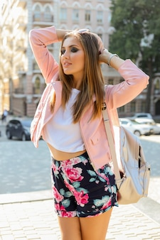 Pretty lond woman posing  on the street. wearing stylish sunglasses, pink leather jacket and back pack.