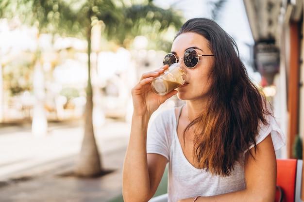 Pretty long hair brunette girl enjoy coffee in street cafe.