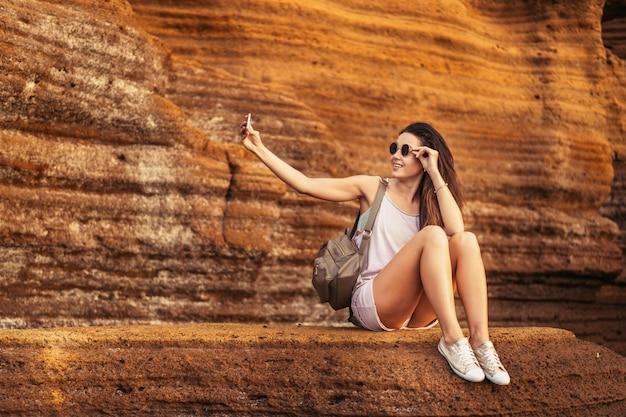 Pretty long hair brunette tourist girl relaxing on the stones near sea.