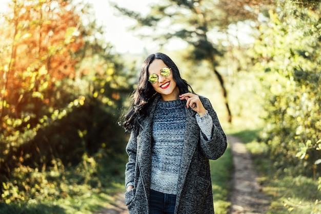 Pretty long hair bruntte girl walking in the autumn forest.