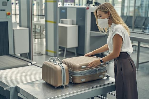 彼女の荷物のチェックをしている間、セミポジションで立っているかなり長い髪のブロンド