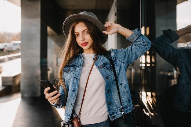外を歩いて電話を待っている黒いスマートフォンを保持しているスタイリッシュなデニムの衣装でかなり長い髪の少女。