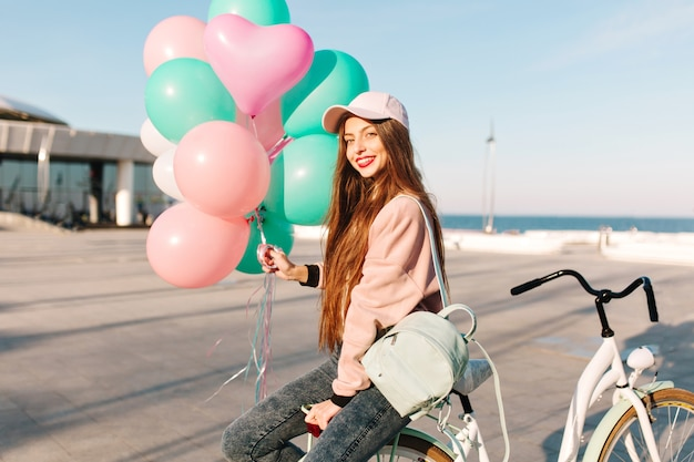 Pretty long-haired girl in pink outfit sitting on the bicycle with balloons waiting for friend from voyage.