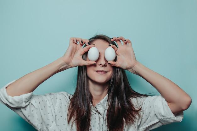Довольно длинноволосая женщина в белой рубашке. женщина держит белые пасхальные яйца вместо глаз. счастливой пасхи.