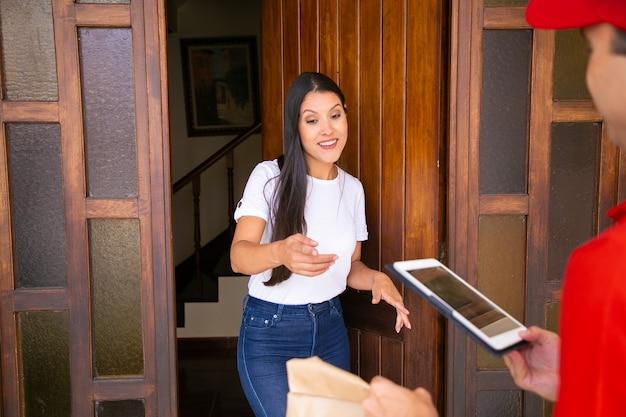 순서를 받고 웃 고 꽤 긴 머리 여자. 여성 고객에게 태블릿을 제공하고 특급 주문을 전달하고 가방을 들고 자른 배달원. 배달 서비스 및 온라인 쇼핑 개념