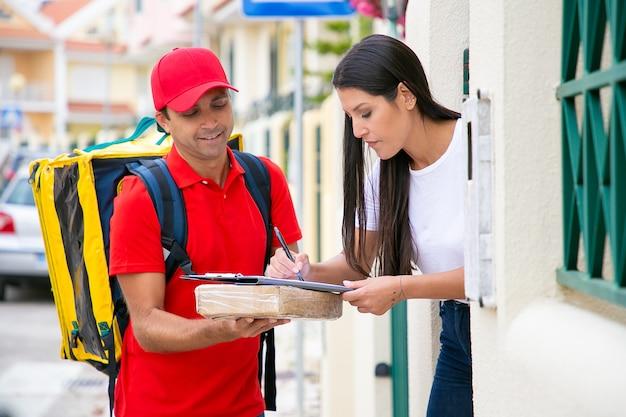 Довольно длинноволосая женщина получает пакет от доставщика. курьер средних лет стоит, улыбается и держит буфер обмена на посылке, когда клиент подписывает квитанцию. служба доставки и почтовая концепция