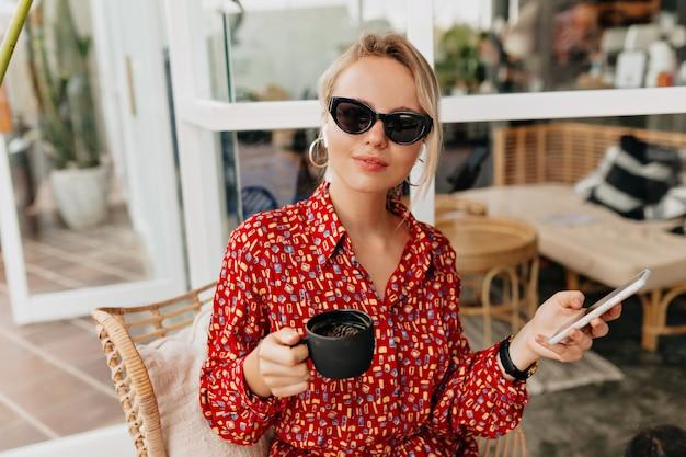 Donna abbastanza amabile in occhiali da sole che indossano musica d'ascolto vestito estivo luminoso, utilizzando smartphone